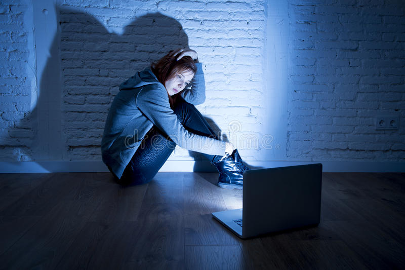 Вспугнутый женский подросток при cyberbullying и домогательство компьтер-книжки компьютера страдая быть злоупотребленным онлайн стоковая фотография