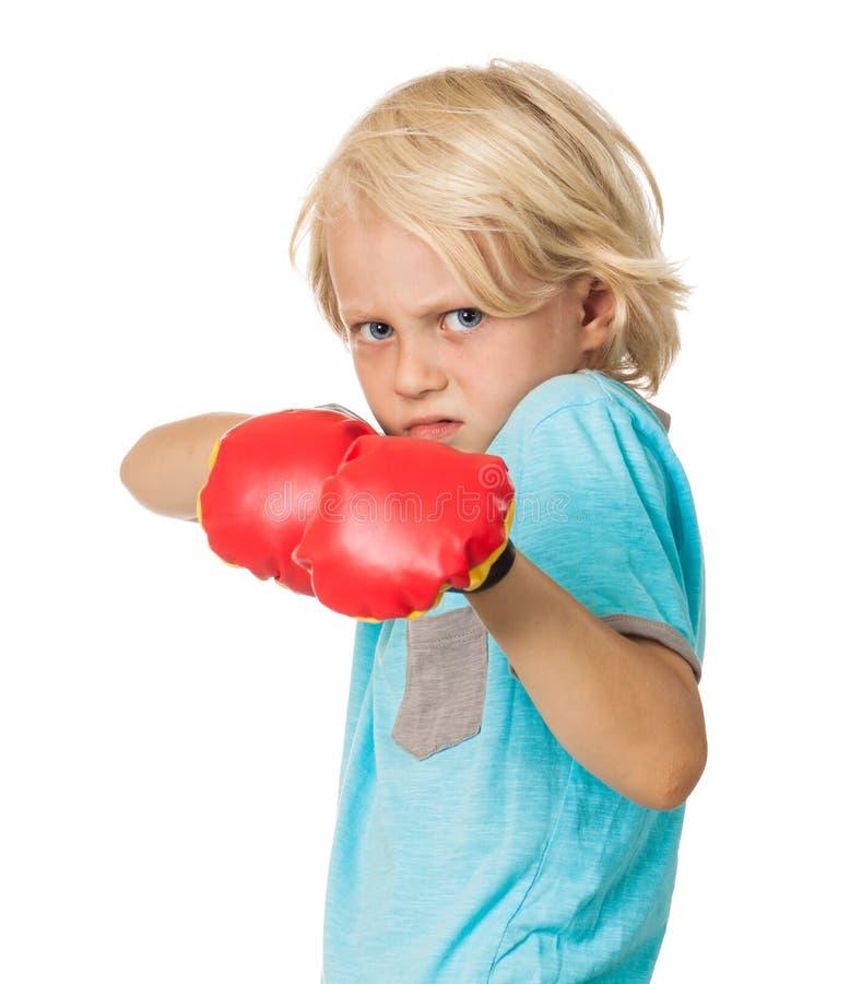 Вспугнутый сердитый мальчик с перчатками бокса стоковое фото rf