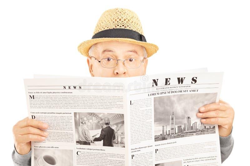 Вспугнутый старший человек при стекла пряча за газетой стоковые фото
