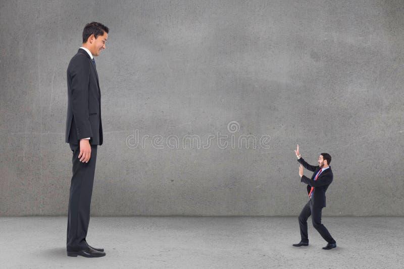Вспугнутый человек мелкого бизнеса смотря человека крупного бизнеса стоковое фото rf