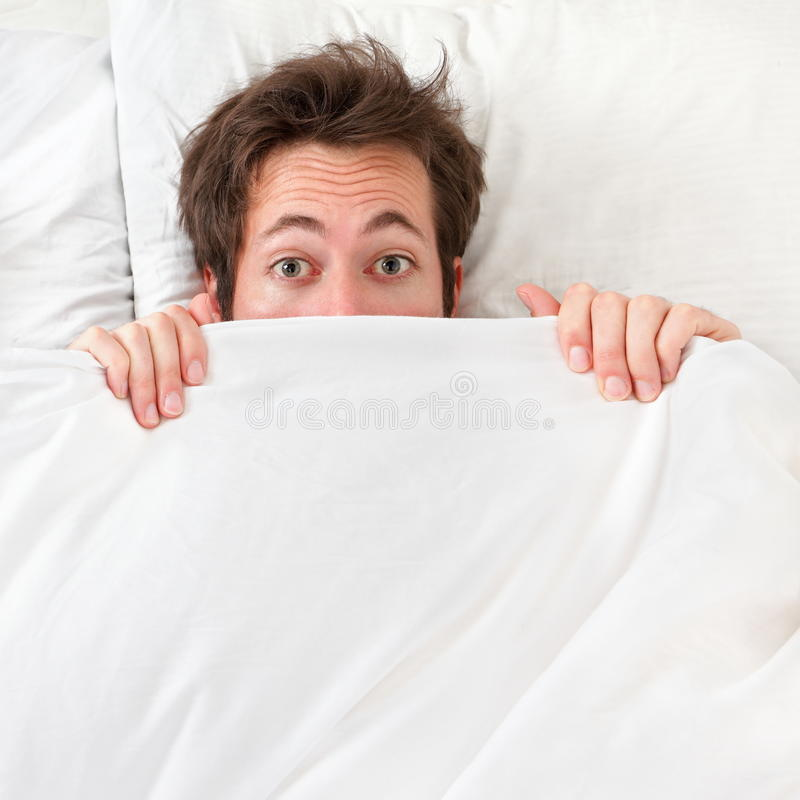 Вспугнутый человек пряча в кровати Стоковое Фото