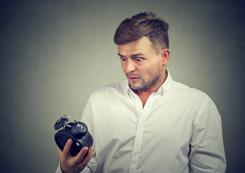 Вспугнутый человек смотря будильник стоковые изображения rf