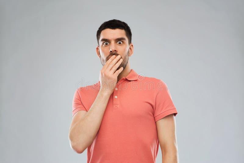 Вспугнутый человек в футболке поло над серой предпосылкой стоковое фото rf