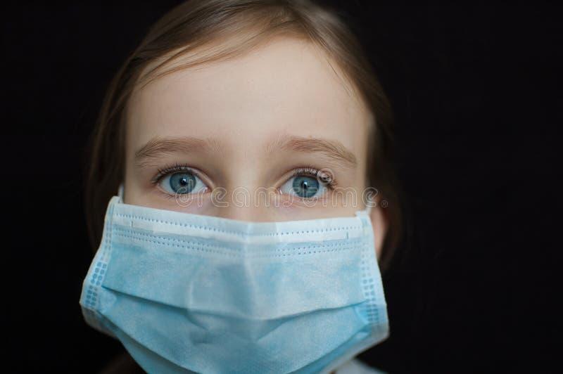 Вспышка коронавируса Covid-19 Маленькая блондинка с голубыми глазами в одноразовой маске для защиты от вируса стоковые изображения