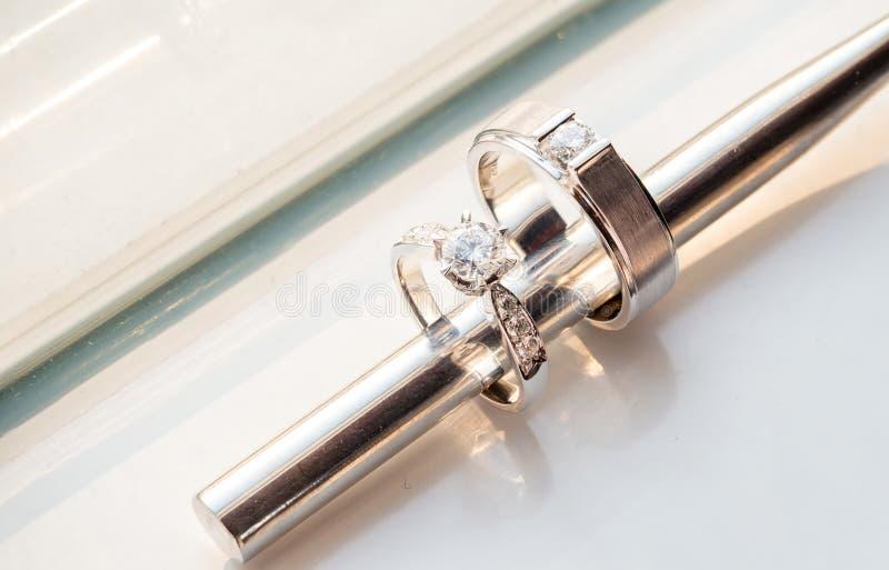 вставка палочки металла внутри 2 обручального кольца диаманта для groom и невесты на белой предпосылке стоковое фото
