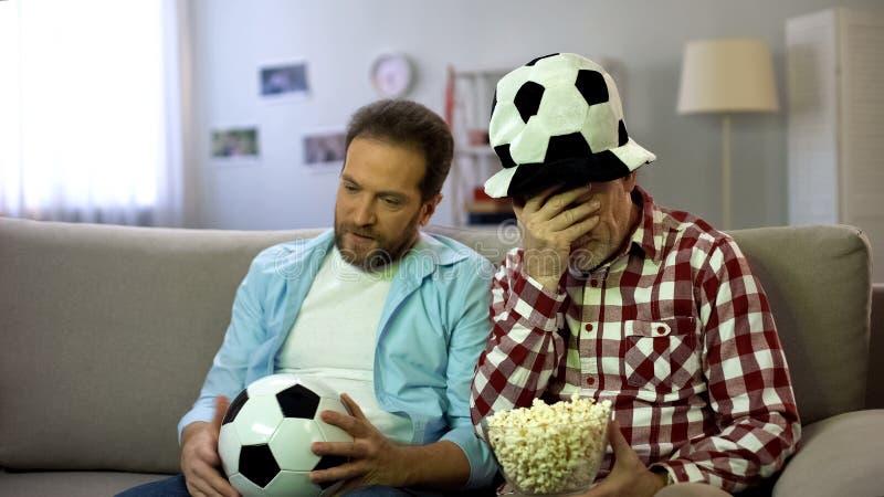 Встревоженные взрослые мужчины смотря футбольный матч по телевизору, несчастный о терять команды стоковые изображения
