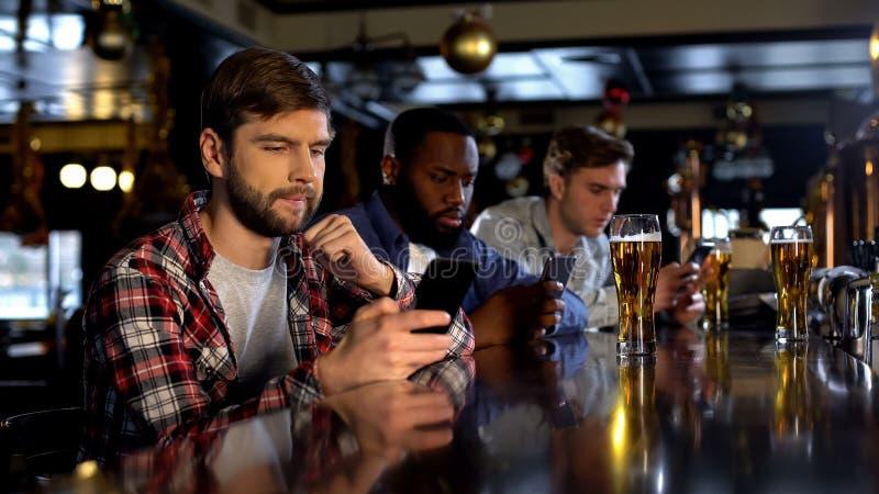 Встревоженные мужские вентиляторы держа пари на телефоне, наблюдая игре в пабе, играя в азартные игры применении стоковое изображение rf