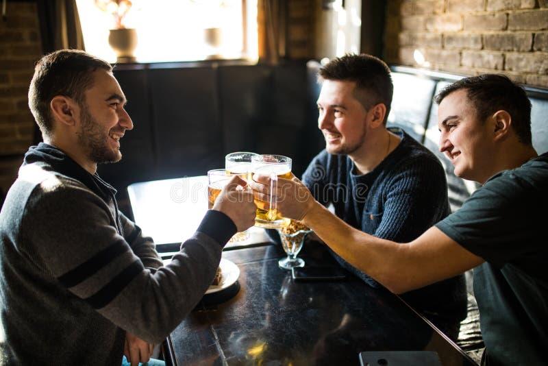Встречать лучшие други 3 счастливых молодого человека в вскользь носке говоря и выпивая пиво пока сидящ в баре совместно стоковые фотографии rf