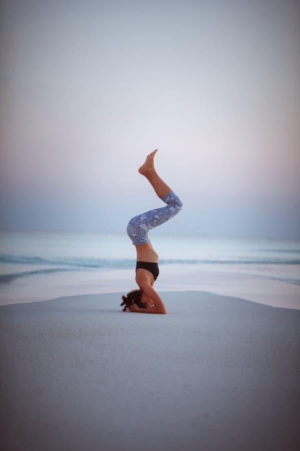 Встреча йоги лета на красивом золотом пляже путешествия йоги Мальдивов, Salamba Sirsasana - поддержанного headstand стоковое фото
