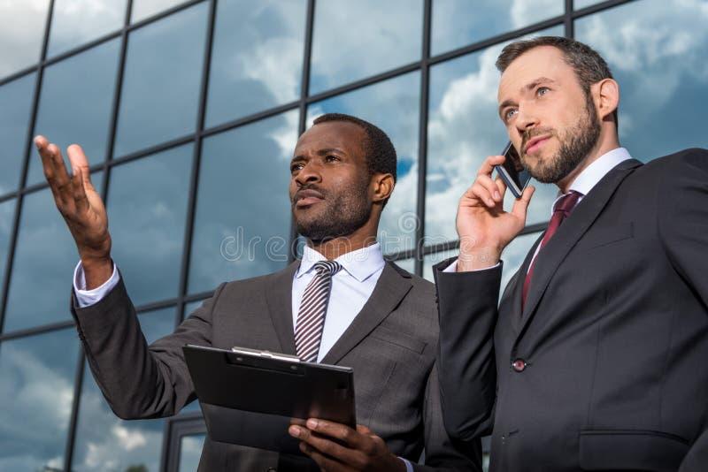 Встреча команды дела и использовать smartphone outdoors около офисного здания стоковые фото