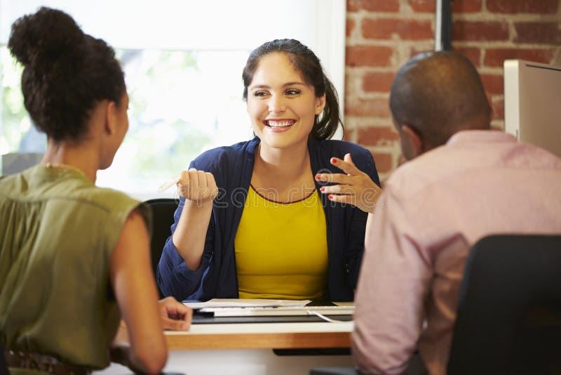 Встреча пар с финансовым советником в офисе стоковая фотография