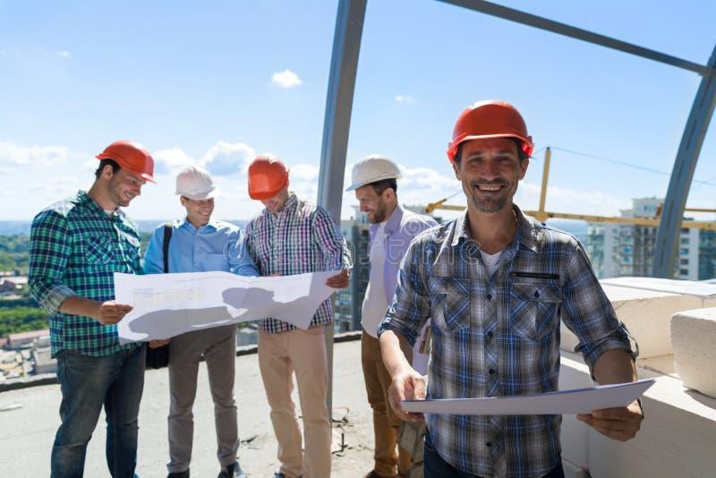 Встреча построителей команды группы в составе Outdoors мастер в защитном шлеме смотря проект Duscussing планов с архитектором стоковая фотография rf