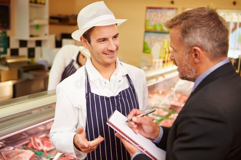 Встреча управляющего банком с предпринимателем магазина мясников стоковое изображение rf