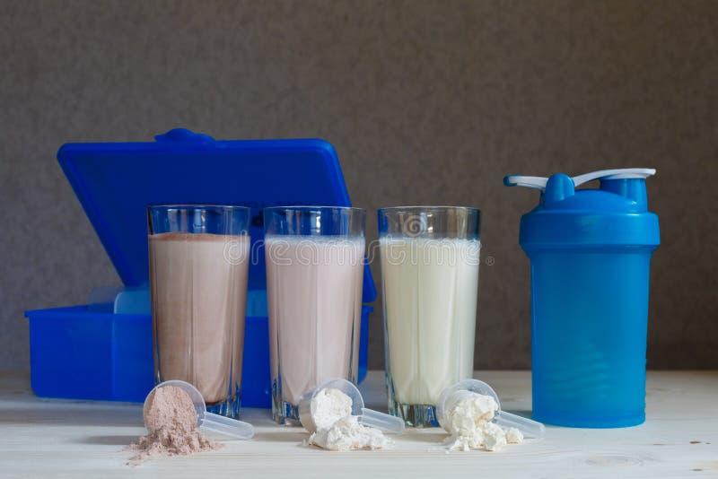 3 встряхивания протеина whey молока в стеклянных чашках аранжированы в ряд с 3 ветроуловителями протеина, коробки еды, шейкера, н стоковые фотографии rf