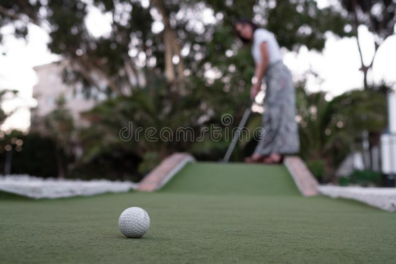 Всход женщины играя minigolf с шариком на переднем плане стоковые изображения rf