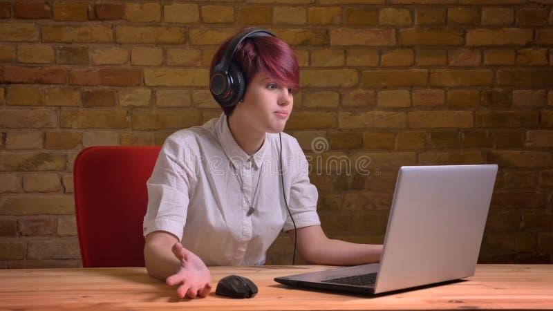 Всход крупного плана блоггера молодого привлекательного хипстера женского видео- в наушниках используя ноутбук и течь в реальном  стоковые изображения rf