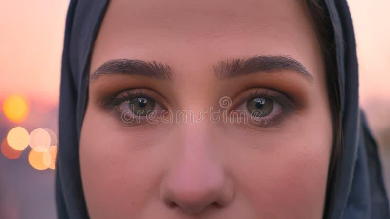 Всход крупного плана молодой привлекательной женской стороны в hijab с серыми глазами смотря прямо на камере с городским городом  стоковые фотографии rf