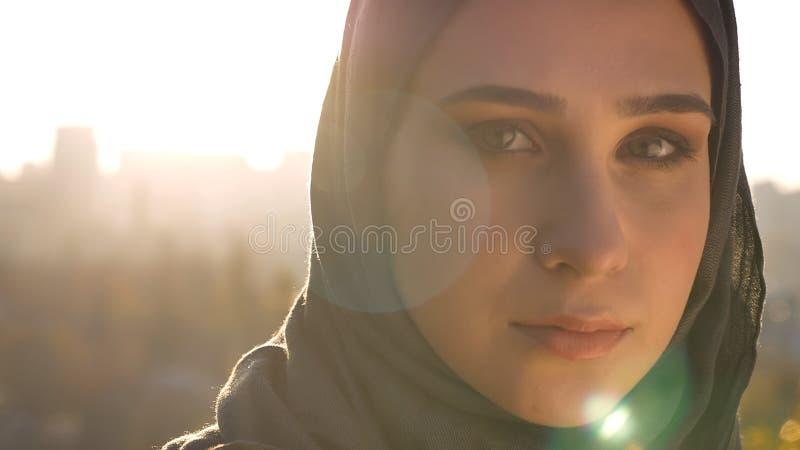 Всход крупного плана молодой привлекательной мусульманской женщины в hijab смотря вперед с солнцем городских условий и светить на стоковые изображения rf