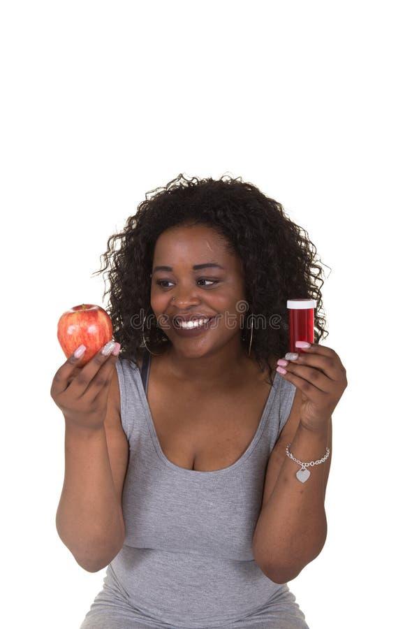 Всход концепции о здравоохранении женщины выбирая между яблоком и бутылкой пилюльки стоковое изображение rf