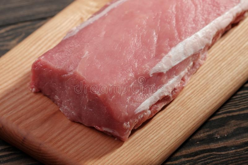 Вся бескостная поясница свинины без тучного конца-вверх Tenderloin свинины на разделочной доске на темной предпосылке стоковая фотография
