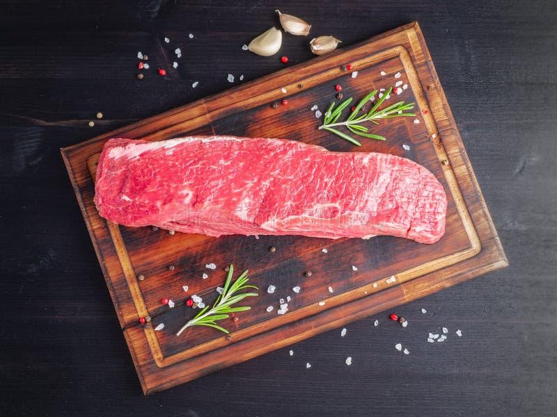 Вся часть сырого мяса Свежее большое striploin говядины со специями дальше стоковое изображение