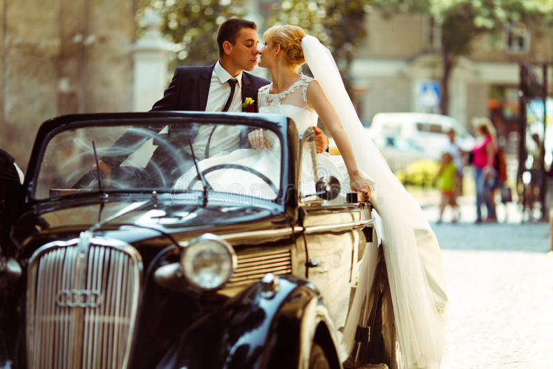 Вуаль невесты висит вниз пока она целует groom сидя на re стоковые изображения