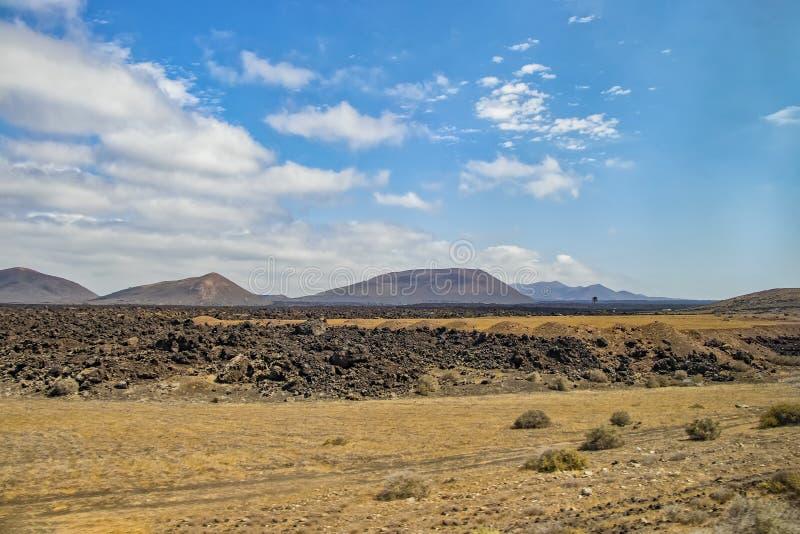 Вулканические холмы в ландшафте пустыни острова Лансароте, который охраняемая территория ЮНЕСКО стоковое фото