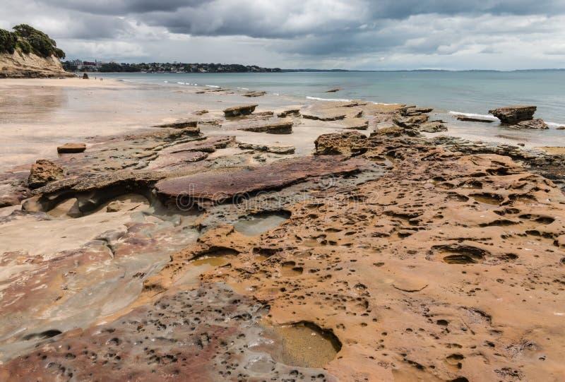 Вулканические породы на пляже во время отлива стоковые фото