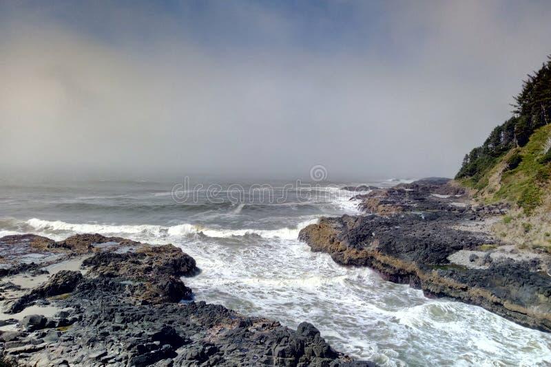 Входящие маслобойки прилива прибоя в узком канале колодца Тора на накидке Perpetua, побережье Орегона стоковое изображение