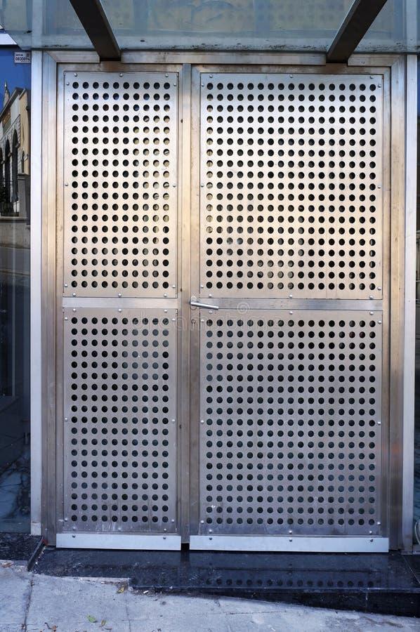 Вход в современное здание Двери металла стальные пефорированные стоковые изображения