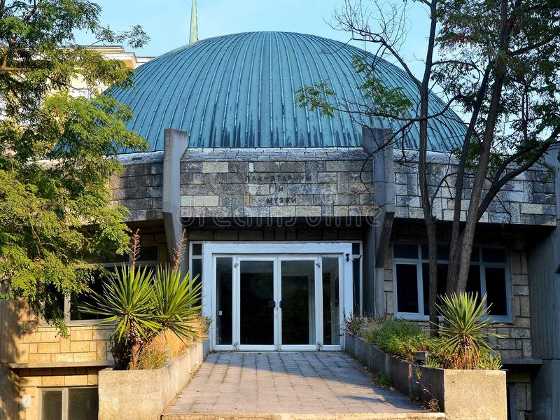 Вход к планетарию и музей с приданной куполообразную форму крышей среди зеленых деревьев и юкк против голубого неба стоковые фотографии rf