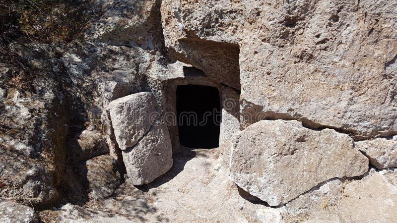 Вход Domus de janas с дверью в Montessu'snecropolis при вход выгравированный в мягком утесе стоковое изображение rf