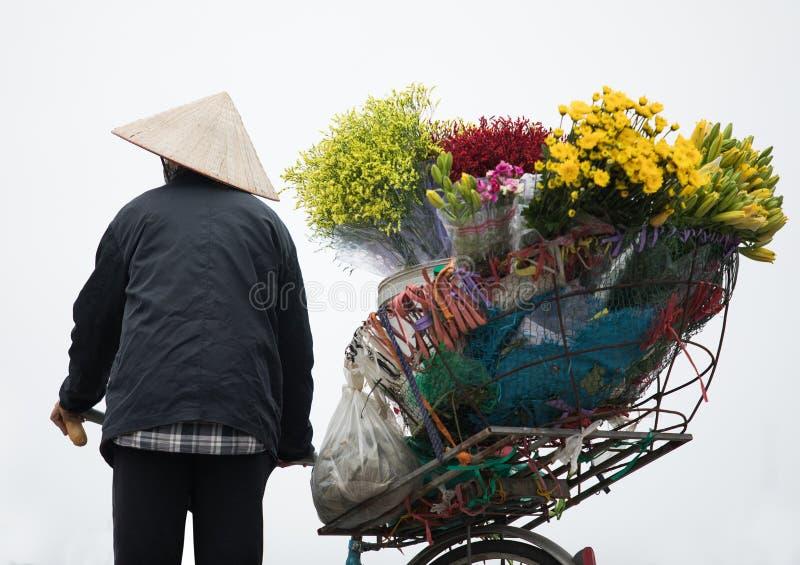 Въетнамская женщина и продавать велосипед цветка в isolat города Ханоя стоковые фотографии rf