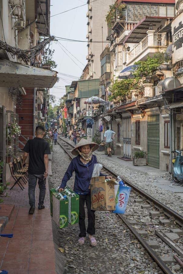 Въетнамская женщина носит картон, который нужно повторно использовать на рельсовом пути в небольшой улице Ha noi, Вьетнама стоковые изображения rf