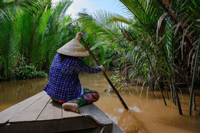 Въетнамская женщина с типичной шляпой гребя деревянную шлюпку через ладони на перепаде Меконга, Вьетнам воды стоковые фото