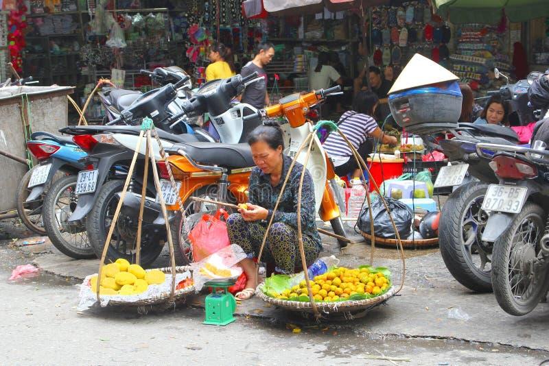 Въетнамская продажа плодов плетеных корзин женщины, Ханой, Вьетнам стоковые изображения
