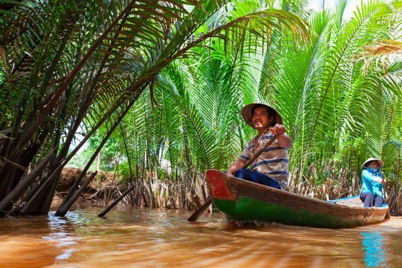 Въетнамские люди на традиционной езде шлюпки каналом Меконга стоковое изображение rf