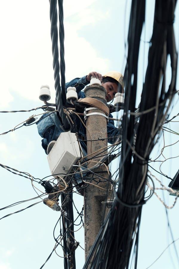 Въетнамский максимум подъема работника электричества на электрическом столбе для того чтобы отремонтировать сеть электричества стоковые фото