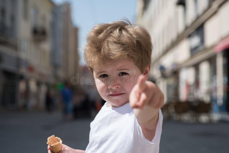 выберите I вы Палец пункта мальчика на улице города Небольшой ребенок со стильной стрижкой Немногое ребенок с короткое белокурым стоковое фото