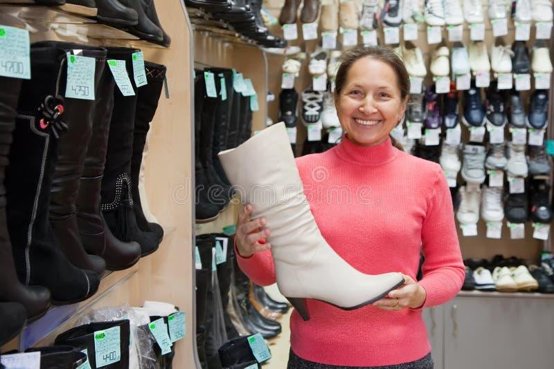 выбирает женщину магазина ботинок зимнюю стоковые изображения