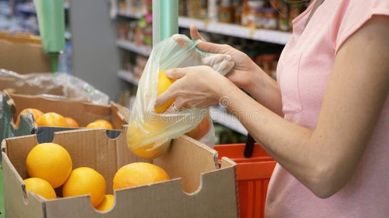 Выбирать молодой женщины апельсины от коробки на супермаркете стоковые изображения rf