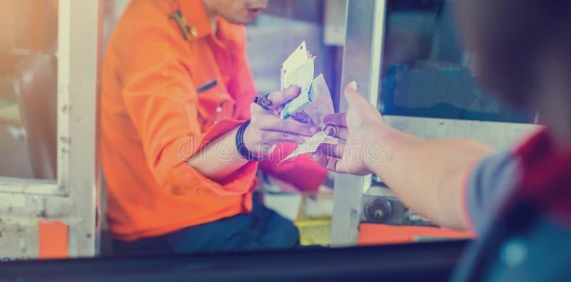 Выборочное внимание водителя оплачивает скоростную дорогу Мужчина платит деньги кассиру за вход на платную дорогу стоковое фото