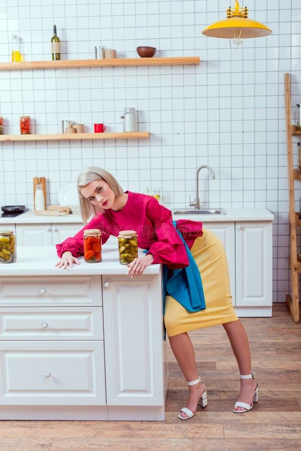 выборочный фокус красивой стильной домохозяйки с консервными банками замаринованных овощей на счетчике стоковое фото rf