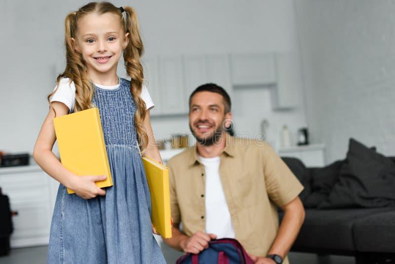 выборочный фокус маленького ребенка с книгами и отцом за дома назад к стоковые фотографии rf