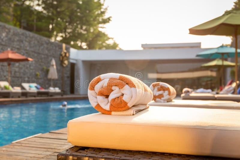 Выборочный фокус на бассейне полотенца на кровати пляжа вокруг бассейна в гостинице стоковые фотографии rf