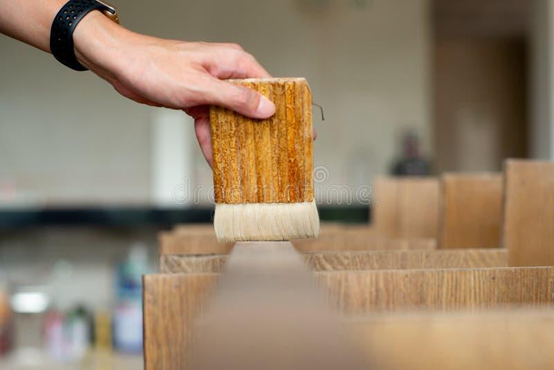 Выборочный фокус на руке плотника держит деревянную кисть и применяется на деревянной поверхности на строительной площадке стоковые фото