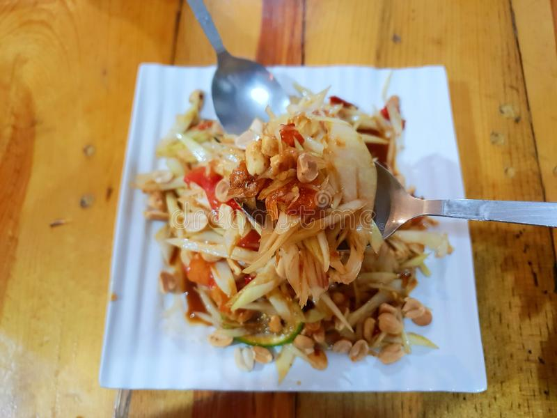 Выборочный фокус салата папапайи в ложке на запачканном салате папапайи стоковые изображения rf