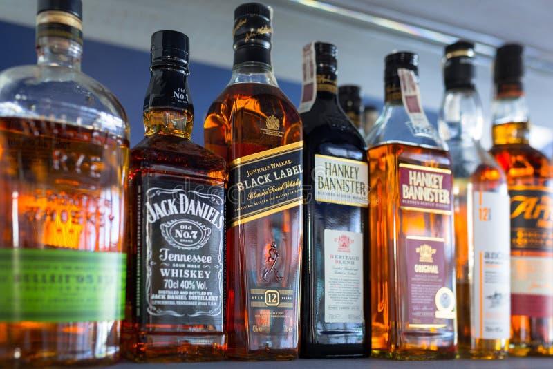 Выбор бутылок вискиа на полке бара стоковые фото