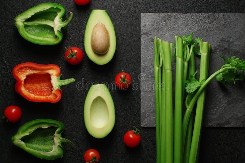 Выбор еды здоровой еды чистый на серой предпосылке Зеленые и красные болгарский перец, авокадо, сельдерей и томаты Взгляд сверху стоковые фото