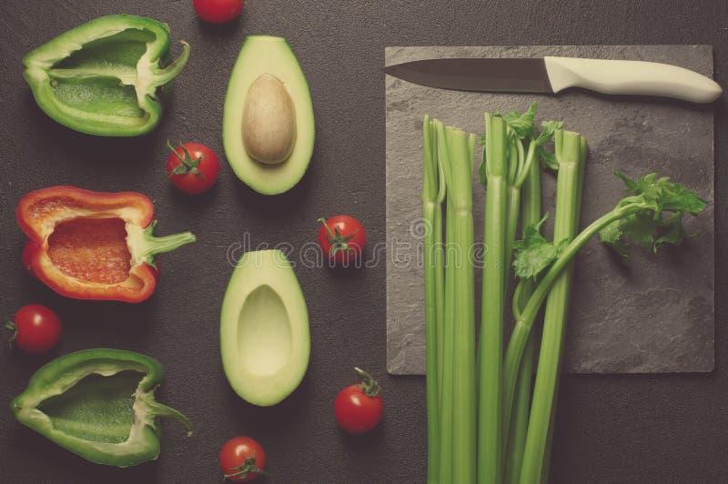 Выбор еды здоровой еды чистый на серой предпосылке Зеленые и красные болгарский перец, авокадо, сельдерей и томаты Взгляд сверху стоковое фото rf
